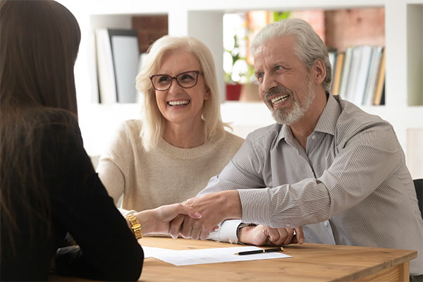 Two older people talking to a lawyer at a desk