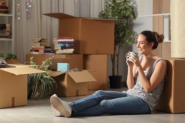 Person sitting on the floor with moving boxes